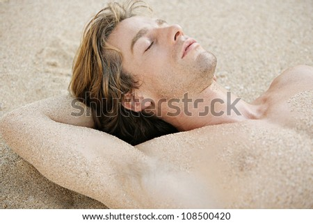 Close up portrait of an attractive young man sleeping on a golden sand beach. - stock photo
