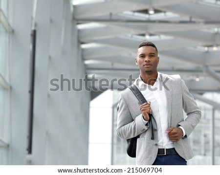 Close up portrait of an attractive young man walking with bag - stock photo