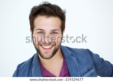 Close up portrait of an attractive young man with beard smiling on white background
