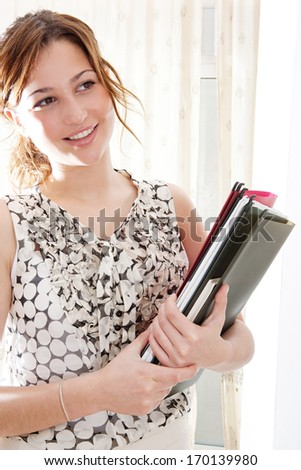 Close up portrait of an attractive young professional business woman holding record files while standing in an office interior with curtains during a sunny day, smiling thoughtful indoors.