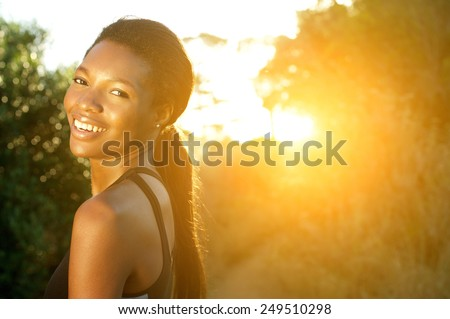 Close up portrait of an attractive young sports woman smiling outdoors - stock photo