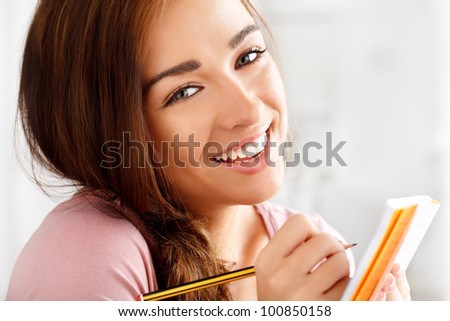Close-up portrait of an attractive young student smiling - stock photo
