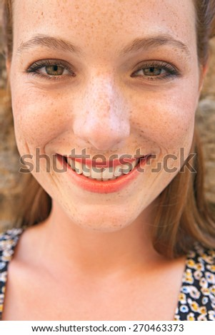 Close up portrait of an attractive young tourist woman visiting a city street with textured stone walls on holiday. Travel and lifestyle vacation living. Joyful and fresh woman portrait, outdoors.