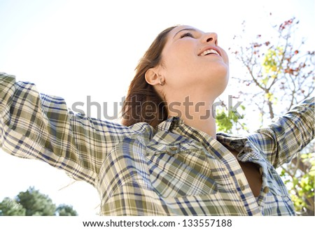 Close up portrait of an attractive young woman enjoying the sun with her arms outstretched and her head leaning back, smiling. - stock photo