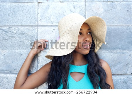 Close up portrait of an attractive young woman smiling with sun hat - stock photo