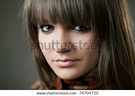 Close up portrait of an attractive young woman standing and posing in a studio