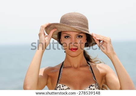 Close up portrait of an beautiful woman with a sun hat on a tropical beach  - stock photo
