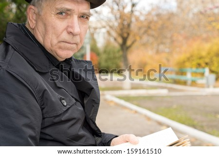 Close up portrait of an elderly man in an overcoat and hat sitting outdoors in the autumn sunshine in a park enjoying the peace while reading his book looking at the camera with a serious expression