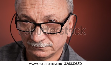 Close up portrait of an elderly man with glasses with copy-space