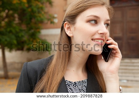 Close up portrait of an elegant professional business woman standing in a city park, smiling and having a phone call conversation with her smartphone device. Business technology outdoors. - stock photo