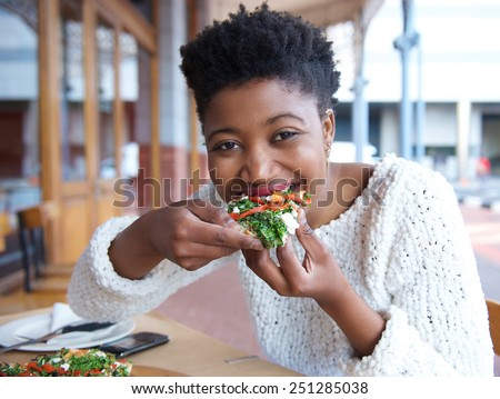 Close up portrait of an happy african american woman eating pizza - stock photo