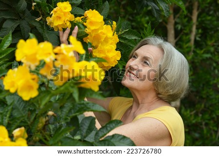 Close-up portrait of an older woman on walk with flowers - stock photo