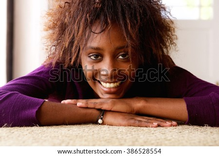 Close up portrait of an smiling young black woman lying down on floor - stock photo
