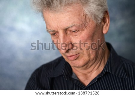 close-up portrait of an thinking elderly man  on a gray background