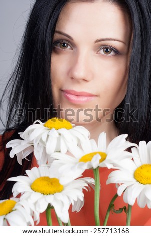 Close-up portrait of an young sexy woman with clean skin and bouquet of flowers. Beauty treatment concept. Camomiles.