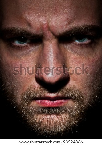 Close-up portrait of angry bearded young man