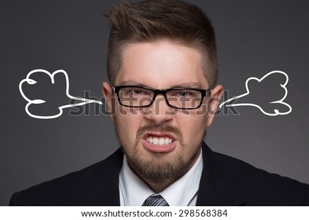 Close-up portrait of angry man with smoke coming out from his ears. Short-haired man in glasses annoying and showing his teeth from anger. - stock photo