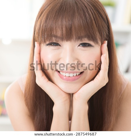 Close up portrait of Asian girl hands holding face, relaxed and smiling at home, woman living lifestyle indoors.