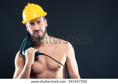 Close up portrait of attractive bearded workman shirtless with drill and yellow helmet, smiling and looking at camera on a gray background