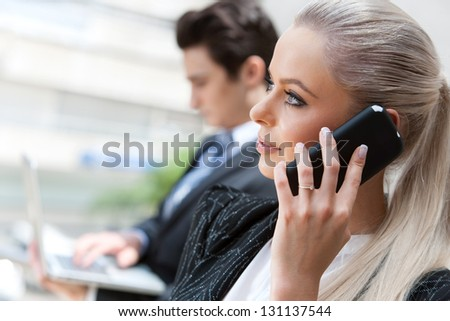 Close up portrait of attractive businesswoman talking on smart phone at meeting. - stock photo