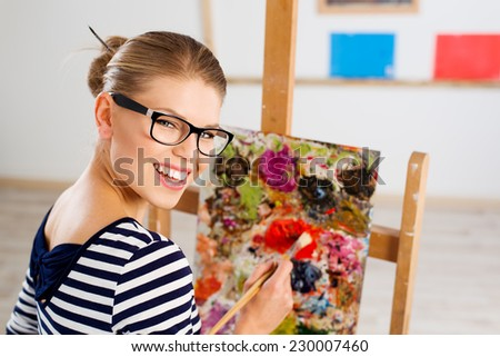 Close-up portrait of attractive cheerful female painter creating new pictorial art. Happy smiling young Caucasian woman with paintbrush standing at easel in her studio.  - stock photo