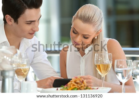 Close up portrait of attractive couple looking at smart phone at restaurant. - stock photo