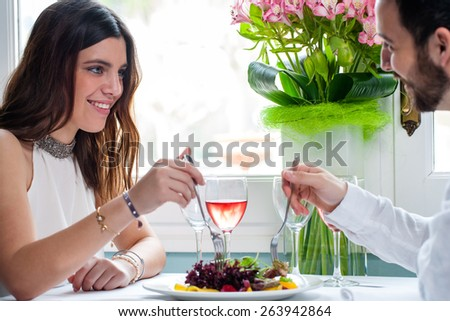 Close up portrait of attractive elegant brunette dining with boyfriend next to window in restaurant. - stock photo