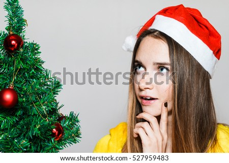 Close-up portrait of attractive fashion Girl in Santa hat  dream face expression.Inspired Thoughts about gifts.Woman near a Christmas tree isolated on white background.New Year and Merry X-mas concept
