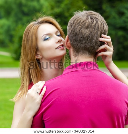Close up portrait of attractive girl embracing her boyfriend outdoors.