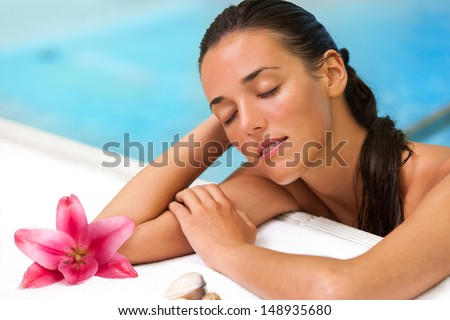 Close up portrait of attractive girl relaxing in spa pool. - stock photo