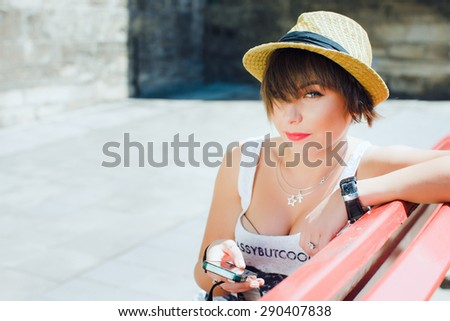 Close up portrait of attractive girl with shortcut dark-blonde hair. Wearing stylish summer hat, white top. Sitting on red bench with mobile phone. Looking at camera. Copy space. - stock photo