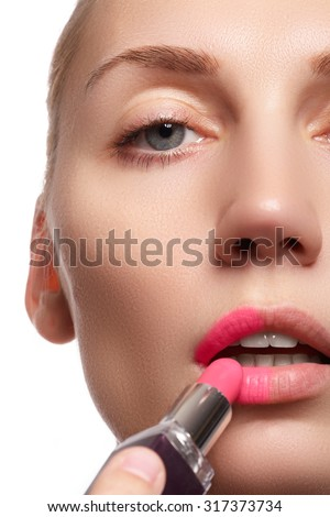Close up portrait of attractive lips of beautiful woman. Rouging her lips with pink mate lipstick. The lady is gently smiling. Close-up of woman applying pink lipstick on her lips