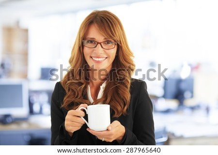 Close-up portrait of attractive middle age businesswoman standing at office and looking at camera while holding mug in her hands.
