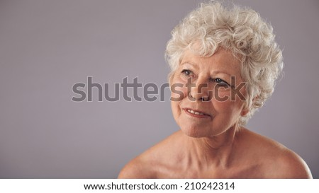Close-up portrait of attractive senior female looking away in thought. Old woman daydreaming against grey background with copy space for your text. - stock photo