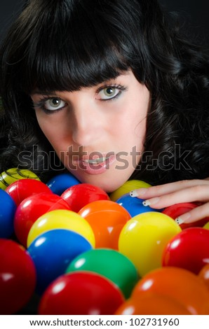 Close up portrait of attractive woman among colorful balls - stock photo