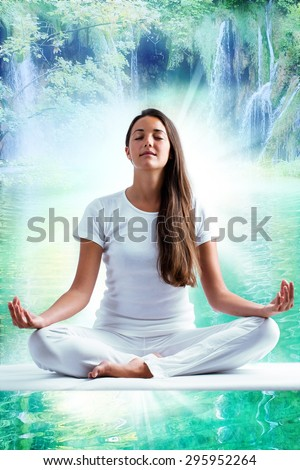 Close up portrait of attractive woman dressed in white meditating. Young girl sitting i yoga position at mystic blue lagoon with waterfalls in background.  - stock photo
