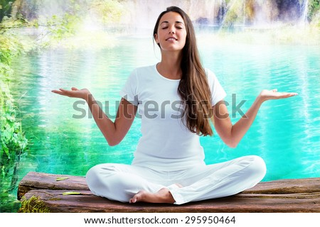 Close up portrait of attractive woman dressed in white sitting in meditating position on wooden log at blue lagoon. Young girl raising hands doing yoga.