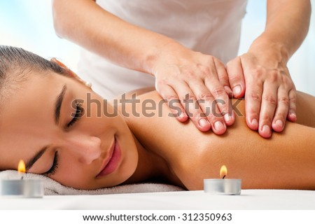 Close up portrait of attractive woman enjoying relaxing massage.Therapist doing manipulative treatment on shoulders.
