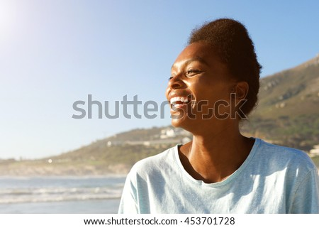 Close up portrait of attractive young african woman standing outdoors and laughing  - stock photo