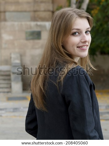Close up portrait of attractive young businesswoman turning and confidently smiling at the camera while standing in the city, outdoors. Business and professional working people. - stock photo
