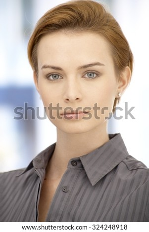 Close-up portrait of attractive young businesswoman with short hair, looking at camera. - stock photo