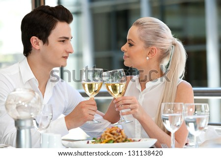 Close up portrait of attractive young couple making a toast at date.