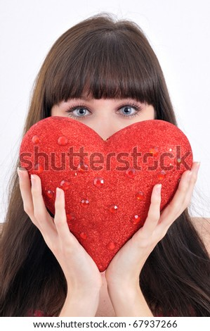 close-up portrait of attractive young girl keeping big red heart in front of her face on white background