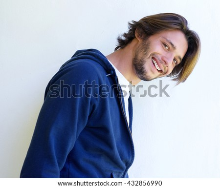 Close up portrait of attractive young man smiling against white wall - stock photo