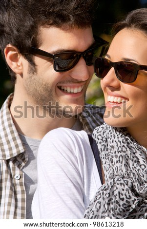 Close up portrait of attractive young smiling couple with sunglasses outdoors. - stock photo