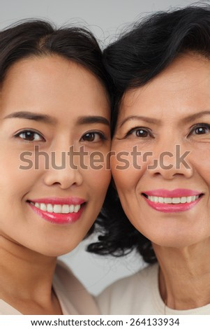Close-up portrait of attractive young woman and her mother looking at the camera - stock photo