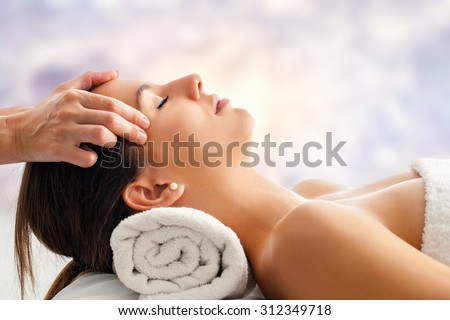 Close up portrait of attractive young woman having relaxing facial massage. Therapist doing head  massage  head against bright colorful background. - stock photo