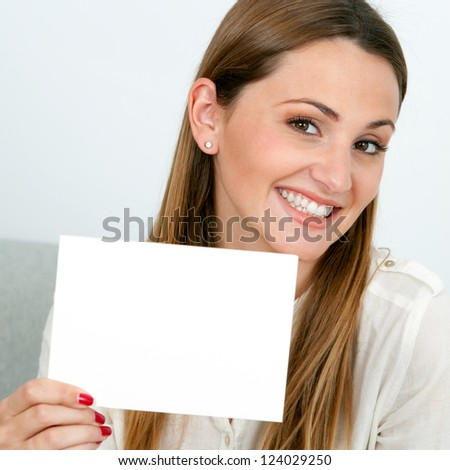 Close up portrait of attractive young woman holding white card.