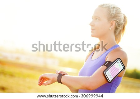 Close up portrait of attractive young woman setting workout on smart watch.Girl in sport wear with fitness chart showing on smart watch.  - stock photo