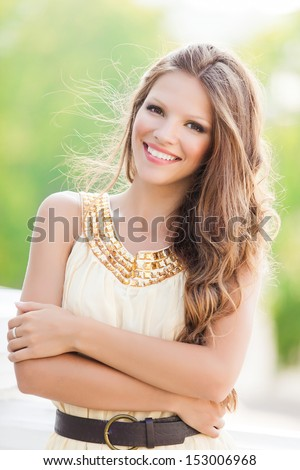 Close up portrait of attractive young woman wearing white dress - stock photo